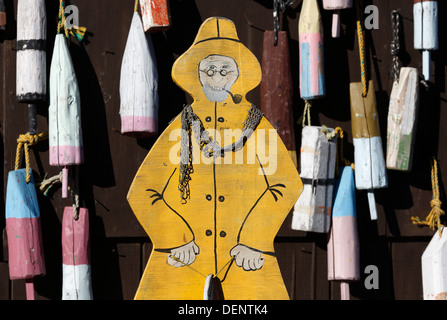 Wooden fisherman cutout and lobster buoys, Maine, USA - Stock Photo