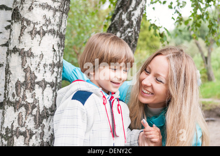 Happy family in the forest, focus on mother - Stock Photo