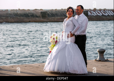 A young couple on their wedding day being photographed at the old Jaffa harbor in Israel - Stock Photo