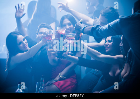 Friends toasting each other in nightclub - Stock Photo