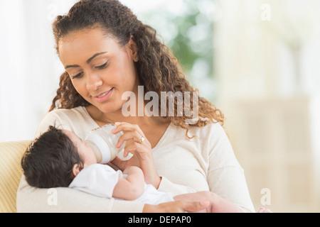 Hispanic mother bottle feeding infant son
