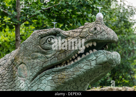 Wine glasses left on one of many dinosaur sculptures, in the dinosaur area of Crystal Palace park, London, England. - Stock Photo