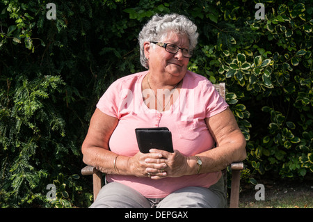 An old / elderly / senior lady (aged 76) sitting in a chair, smiling and enjoying the sunshine in her garden. Taken - Stock Photo