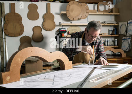 Guitar maker working on plans for an acoustic guitar in workshop - Stock Photo