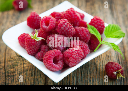 Fresh and ripe raspberries on small plate - Stock Photo