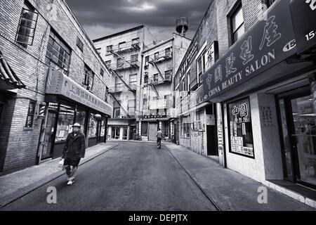 Chinesse walking by in Chinatown, Manhattan, NYC, USA - Stock Photo