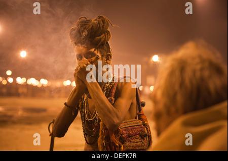 Sadhu smoking at Maha Kumbh, Allahabad, Uttar Pradesh, India - Stock Photo