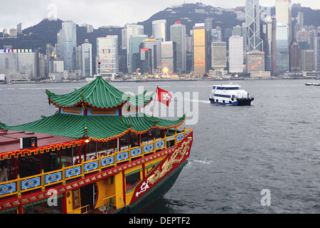 Junk restored as restaurant boat in the bay in front of Hong Kong Island with Hong Kong´s skyline in the early evening - Stock Photo