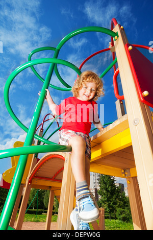 Happy little three years old child boy riding climbing and sliding on playground - Stock Photo