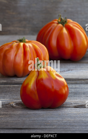 Three large Beefsteak Tomatoes fresh from the Weekly Market on a old wooden Table - Stock Photo
