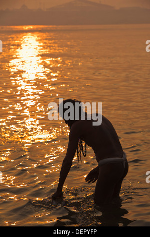 Sadhu taking a holy dip in Ganges River at Maha Kumbh, Allahabad, Uttar Pradesh, India - Stock Photo