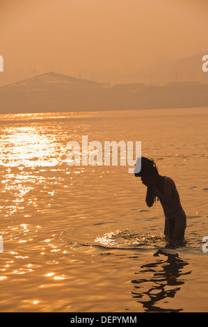 Sadhu taking a holy dip and praying in Ganges River at Maha Kumbh, Allahabad, Uttar Pradesh, India - Stock Photo