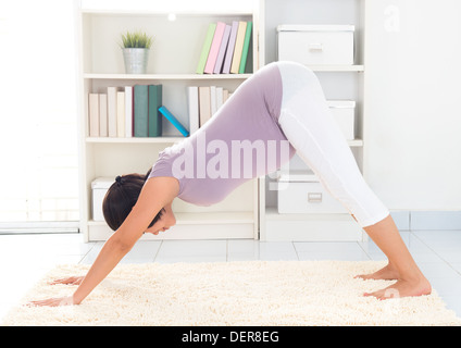 Prenatal yoga meditation. Full length healthy 8 months pregnant calm Asian woman meditating or doing yoga exercise - Stock Photo