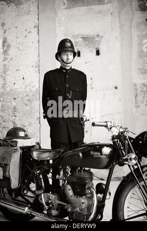 Man in 1940's 40s police uniform and Royal Enfield motor bike - Stock Photo