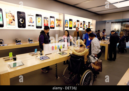 Disabled woman in a wheelchair shopping in the Apple store, Grand Arcade, Cambridge UK - Stock Photo