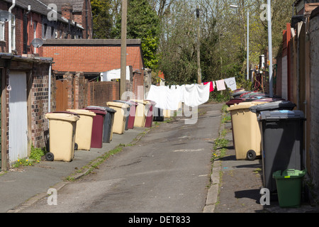 A back street, with washing drying on the line and bins outside, between two rows of terraced houses in Bolton Lancashire - Stock Photo