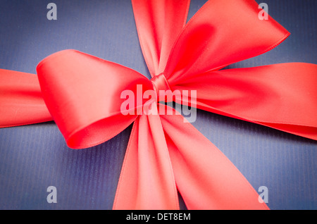 red ribbon on blue background - Stock Photo