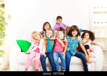 Group of seven happy little 5-6 years old kids, boys and girls, black, Asian and Caucasian sitting on the coach - Stock Photo