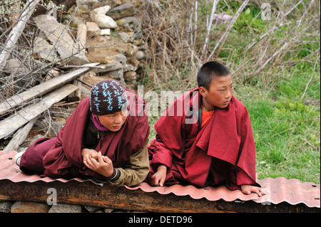 Young monks watching dancers at Domkhar Tsechu festival held in a monastery in the village of Domkhar, Bumthang, - Stock Photo