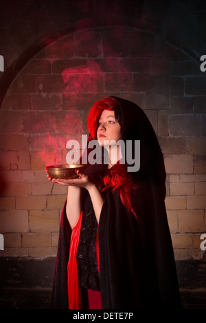 Vampire woman or gothic sorceress with red smoke in a bowl - Stock Photo