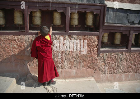 A novice monk spinning the prayer wheels Tiksey, Ladakh, India - Stock Photo
