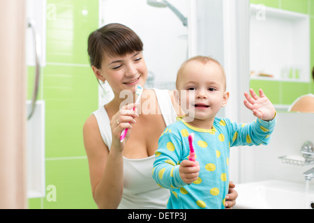mother with baby brushing teeth - Stock Photo
