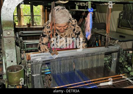 silk production, usbek woman working on a mechanical loom, Silk Road, Fergana Valley, Uzbekistan, Central Asia - Stock Photo
