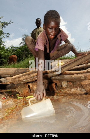 Village children collect water from a dirty water source in the Lira district of northern Uganda - Stock Photo