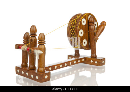 Miniature replica of traditional spinning wheel isolated in white - Stock Photo