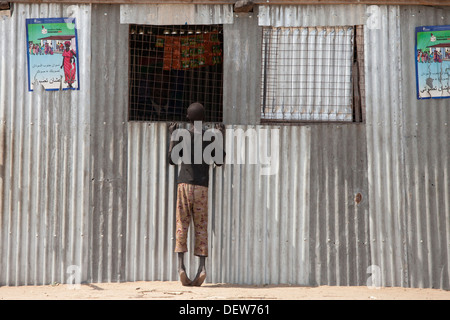 boy looking in shop window of registration place for vote on referendum, Juba Sudan, Dec 2010 - Stock Photo