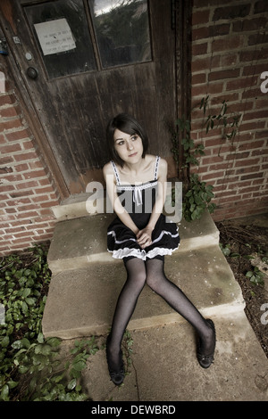 Young woman, wearing fishnet stockings, sitting on concrete steps. - Stock Photo