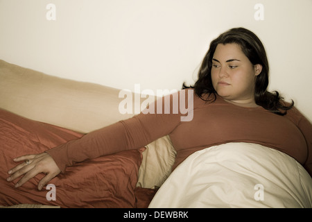 Young woman sitting on her bed. - Stock Photo