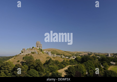 View over trees to ruins of Corfe Castle with village of Corfe in background , Isle of Purbeck Dorset England - Stock Photo