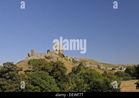 View over trees to ruins of Corfe Castle with town of Corfe in background , Isle of Purbeck Dorset England - Stock Photo
