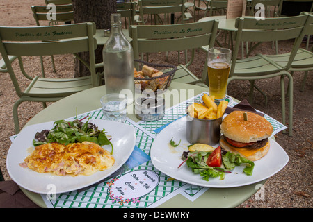two plates of lunch omelette burger fries beer - Stock Photo