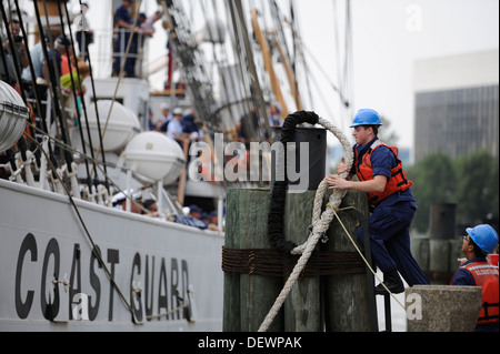 A Coast Guard member from Sector Hampton Roads hooks a mooring line from the Coast Guard Cutter Eagle around a dolphin - Stock Photo