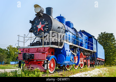 The ancient steam locomotive stands on a pedestal - Stock Photo