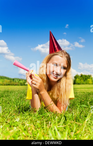 Beautiful little girl with noisemaker horn and birthday party cap laying outside with happy expression on sunny - Stock Photo