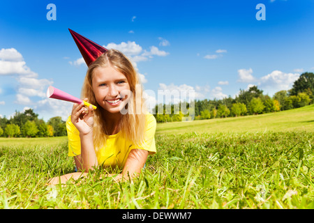 Portrait of teen little girl with noisemaker horn and birthday party cap laying outside with happy expression on - Stock Photo