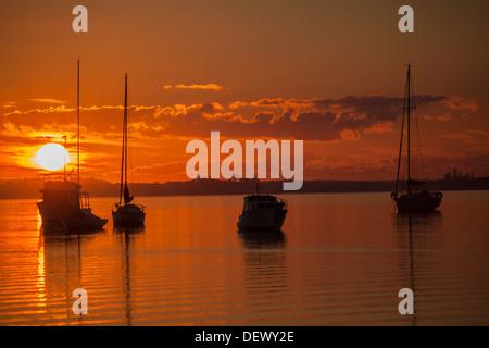 Orange Sunrise with silhouetted boats on Lake Macquarie NSW Australia - Stock Photo