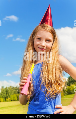 Beautiful little girl with noisemaker horn and birthday party cap standing outside with happy expression on sunny - Stock Photo