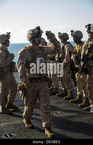 U.S. Marines assigned to Company L, Battalion landing Team 3/2, 26th Marine Expeditionary Unit (MEU), are briefed on target iterations during a live fire exercise on the flight deck of the USS San Antonio (LPD 17), at sea, Sept. 12, 2013. The 26th MEU is
