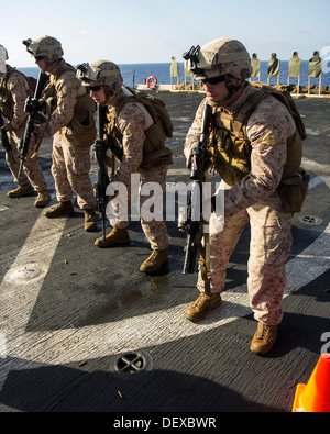 U.S. Marines assigned to Company L, Battalion landing Team 3/2, 26th Marine Expeditionary Unit (MEU), prepare to fire on targets during a live fire exercise on the flight deck of the USS San Antonio (LPD 17), at sea, Sept. 12, 2013. The 26th MEU is a Mari