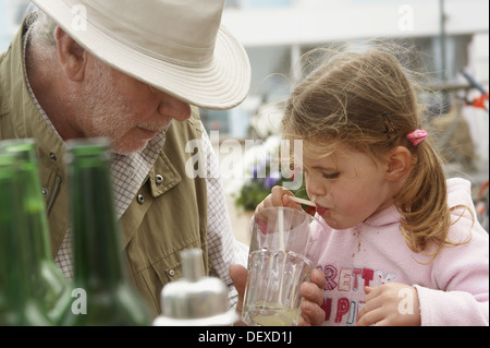 Grandad helping his 3 year old grandaughter with her drink in an outside café - Stock Photo