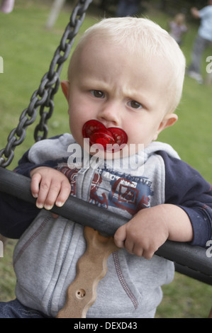 18 Month Old Boy Sitting In A Swing With Dummy Scouling Into Camera
