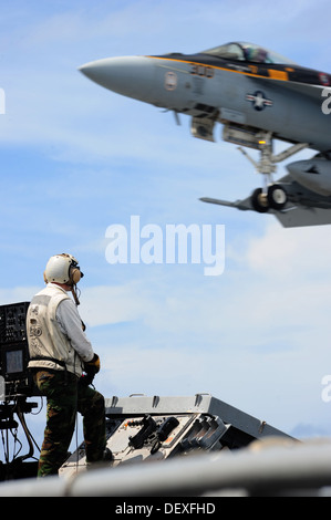 landing signal officer observes an F/A-18E Super Hornet from the Eagles of Strike Fighter Squadron (VFA) 115 as - Stock Photo