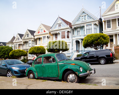 A green Volkswagen Beetle parked in front of the 'Painted Ladies' row of Victorian Houses on Steiner Street in San - Stock Photo