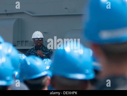 Commander, Expeditionary Strike Group 3 Rear Adm. Frank L. Ponds addresses the crew of amphibious assault ship USS - Stock Photo