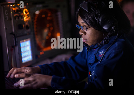Operations Specialist 2nd Class Bianca Ealy stands watch in the combat information center aboard the guided-missile - Stock Photo