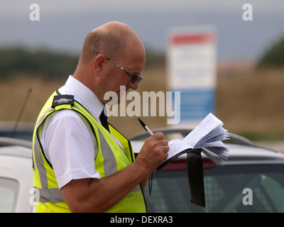 Civil Enforcement Office / Traffic warden writing in his notebook before giving a parking ticket, Exmouth, Devon, - Stock Photo
